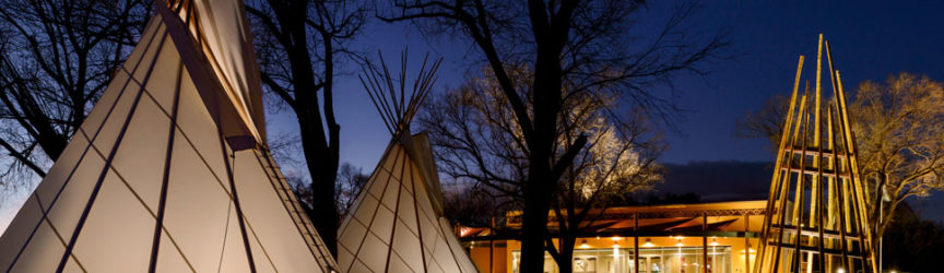 An exterior view of the Ute Indian Museum at dusk, with tepees and a wikiup sculpture in front.