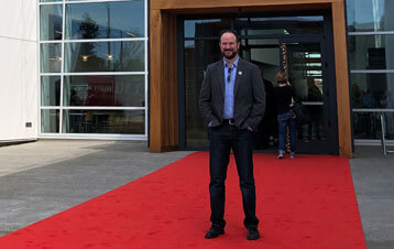 Michael standing on red carpet in front of building