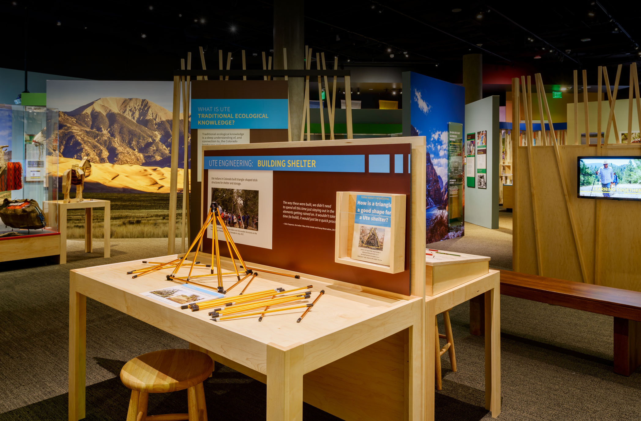 A table with a building interactive in front of a room of exhibits that include large scale landscape photographs