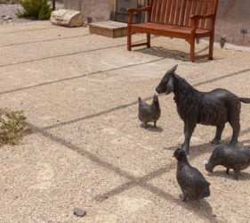 Realistic statues of a goat and chickens outside of an old building.