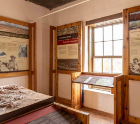 Interpretive panels in both English and Spanish surround a window