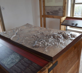 A tactile map sits in the center of one exhibit room
