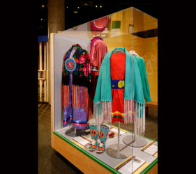 Artifact case full of colorful shawls, dresses, and boots